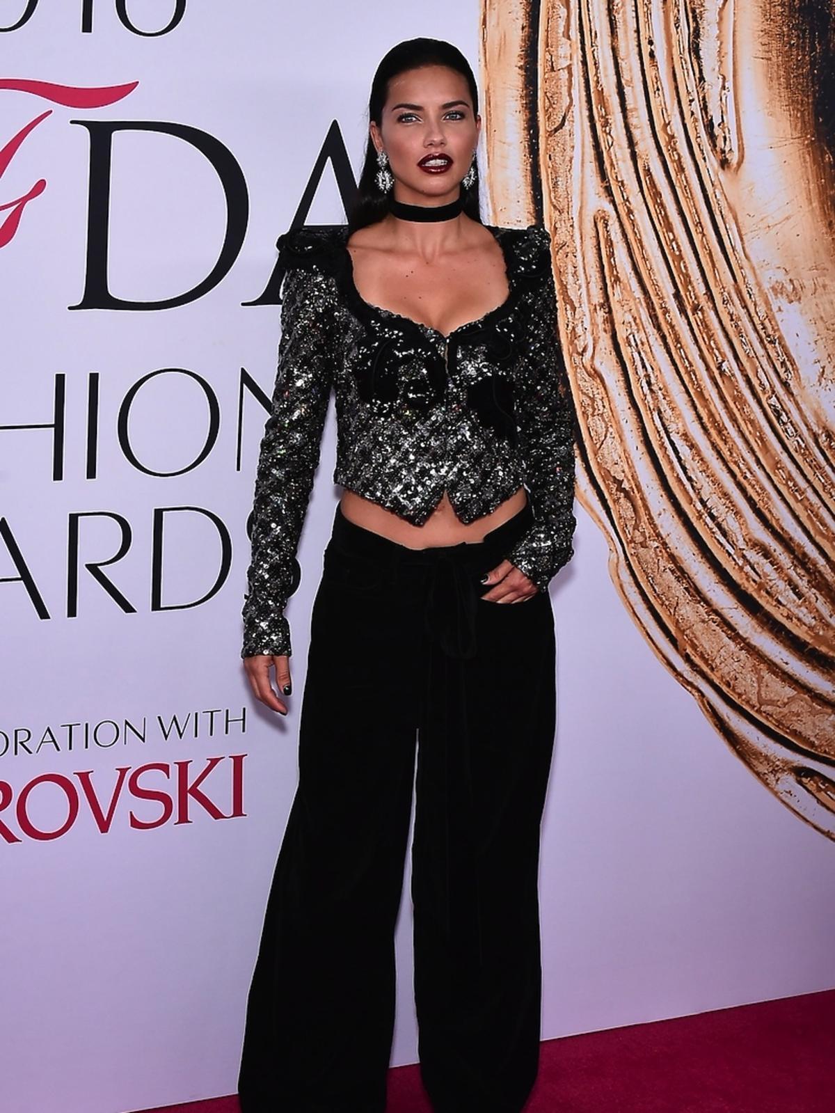 Adriana Lima w czarnych spodniach i bluzce z dekoltem