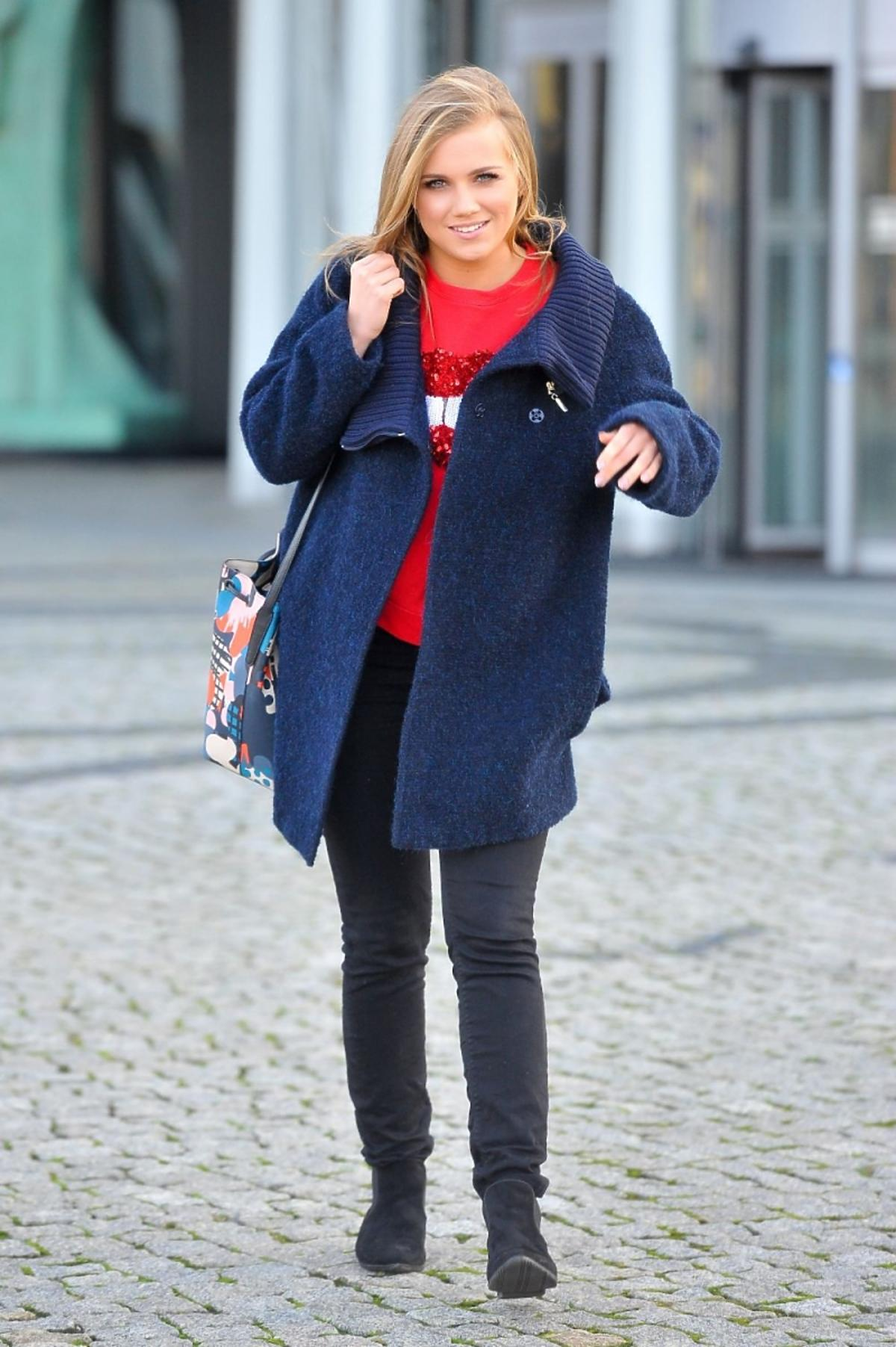 Agnieszka Kaczorowksa w czerwonym swetrze i niebieskiej kurtce
