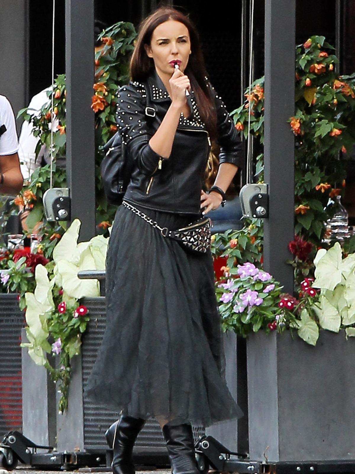 Agnieszka Włodarczyk w szarej spódnicy na ulicy z e-papierosem