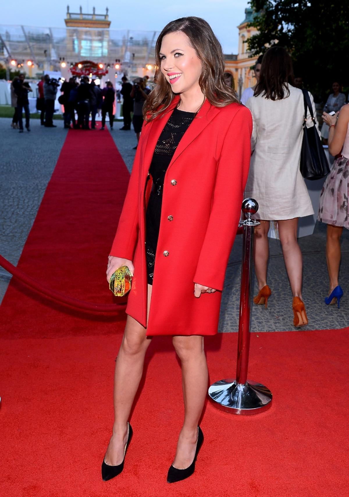 aleksandra kwaśniewska stoi na czerwonym dywanie w czerwonym płaszczu
