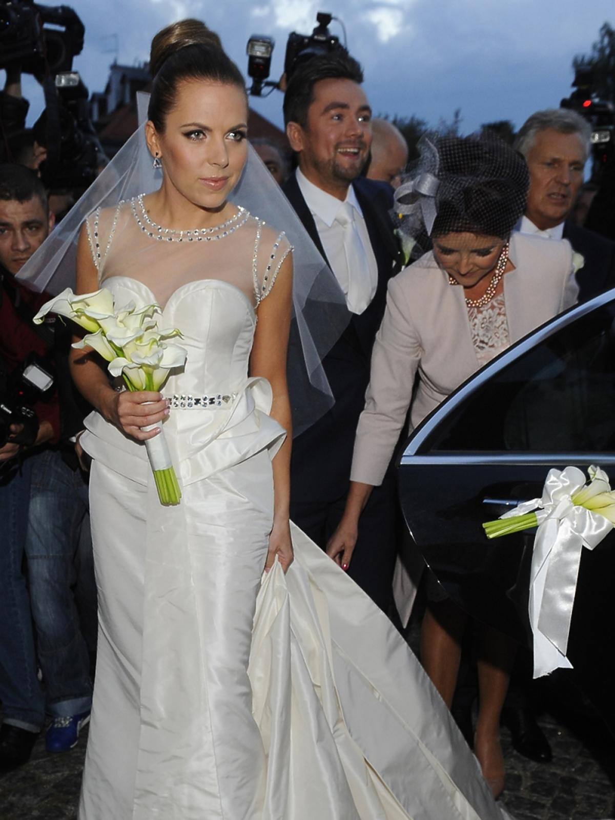 Aleksandra Kwaśniewska w sukni ślubnej w koku z welonem i bukietem kwiatów