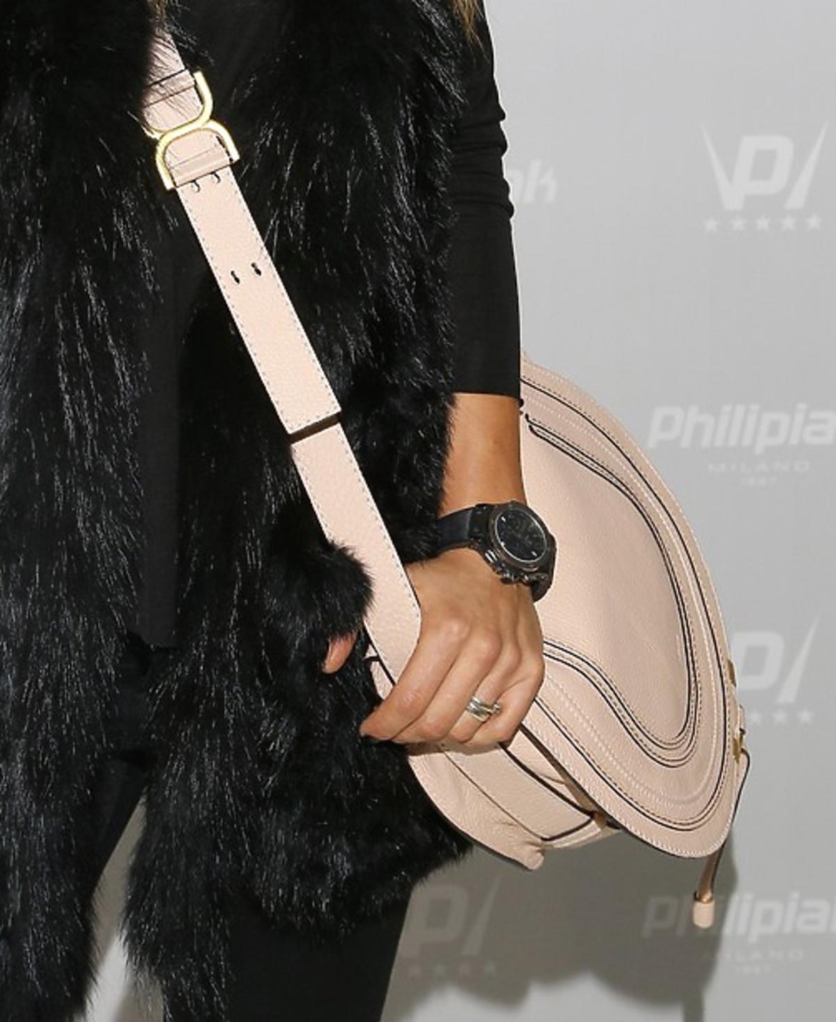 Anna Lewandowska w czarnych spodniach i futerku z pastelową torbą i w butach w kolrze pudrowego różu