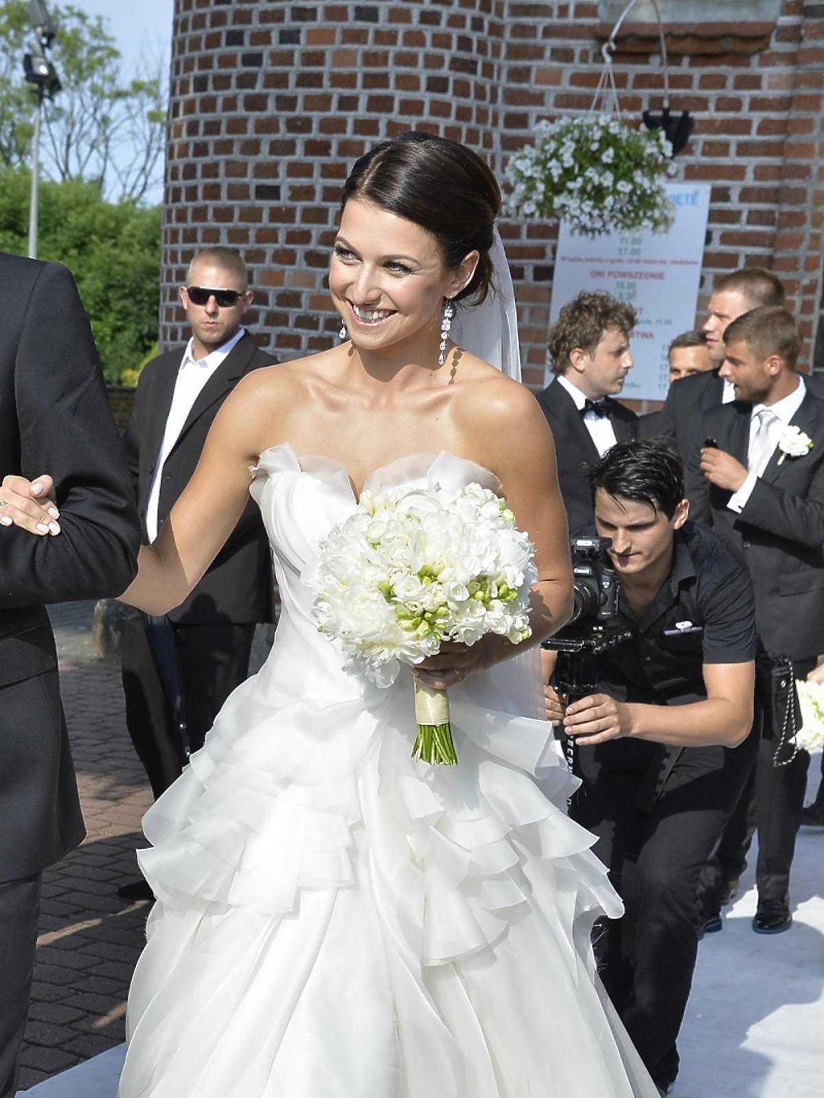 Anna Lewandowska w sukni ślubnej z welonem i bukietem kwiatów i wiszących kolczykach