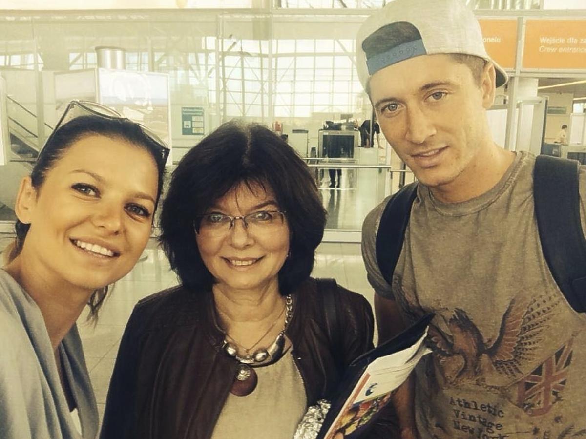 Anna Lewandowska w szarej luzie, Maria Stachurska w czarnej kurtce, Robert Lewandowski w czapce na lotnisku