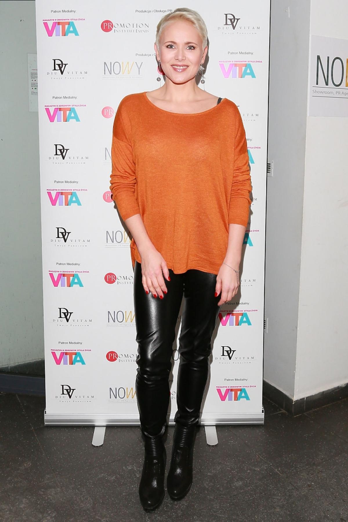 Anna Samusionek w pomarańczowym swetrze