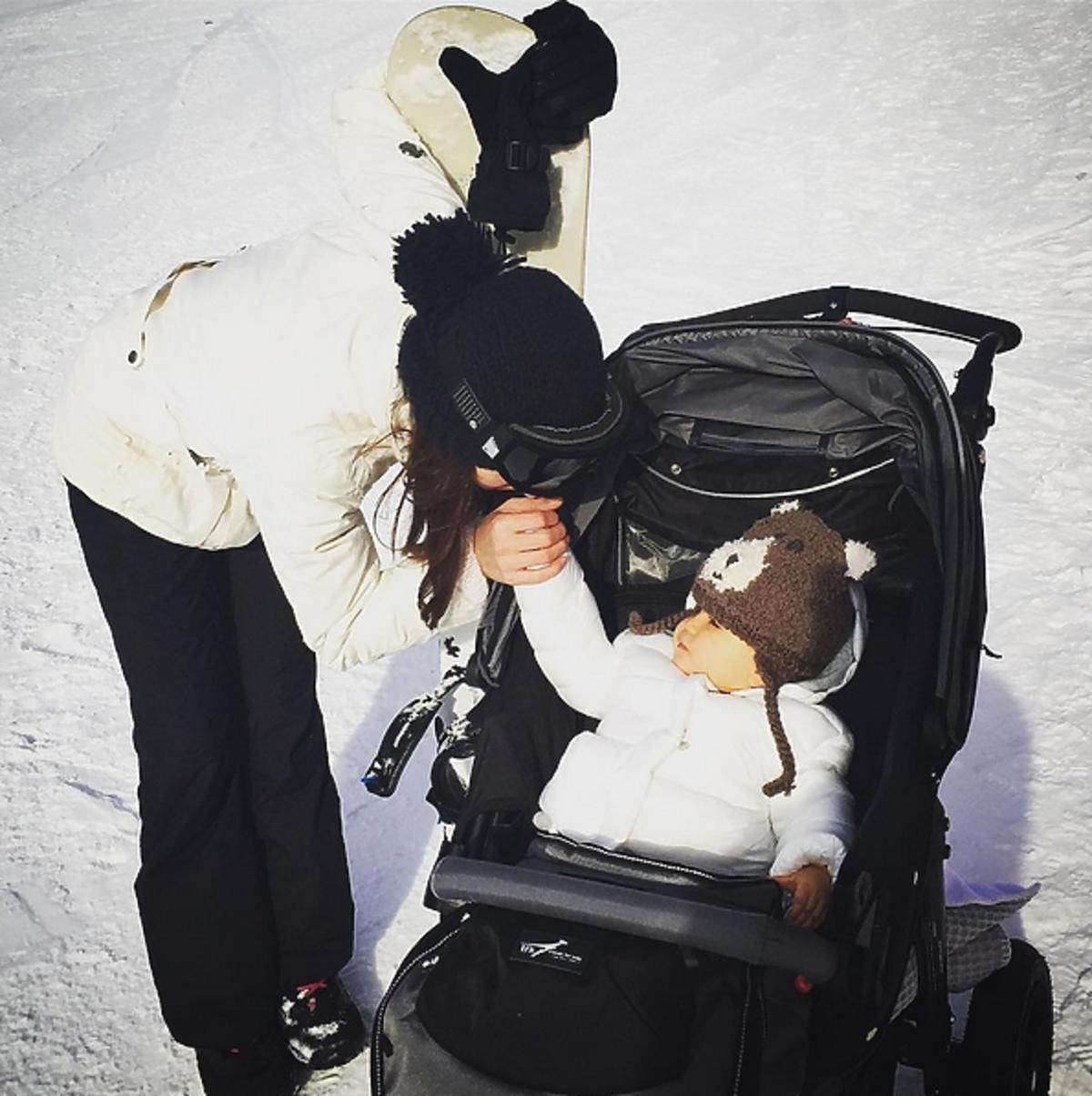 Anna Wendzikowska w czarnej czapce z córką Kornelią w wózku na stoku
