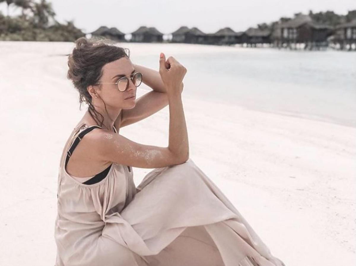 Anna Wendzikowska w jasnej sukience na plaży