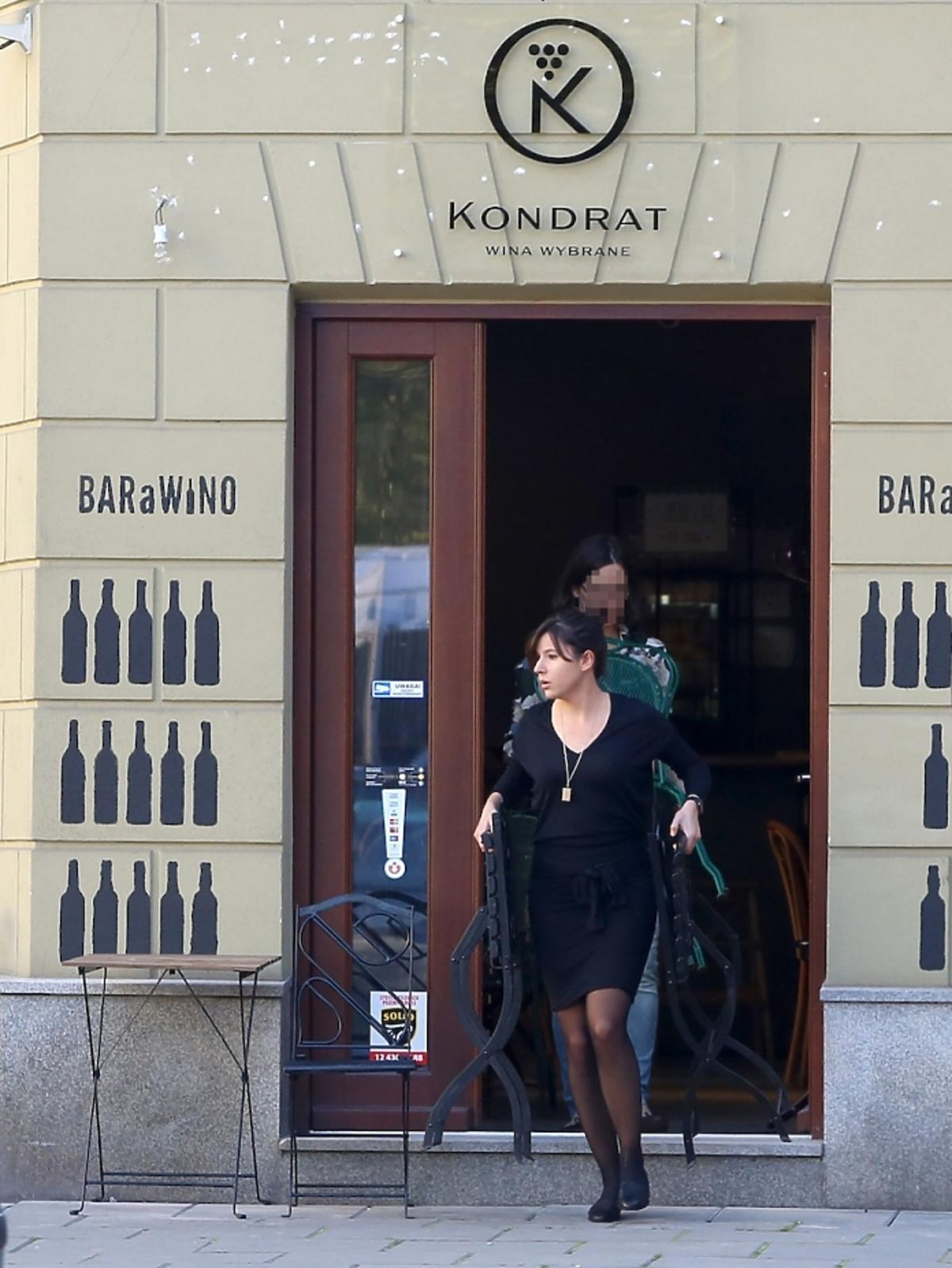 Antonina Kondrat w czarnej sukience niesie krzesło