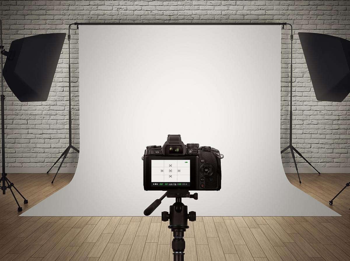 aparat na statywie, dwie lampy do zdjęć, białe tło zdjęciowe