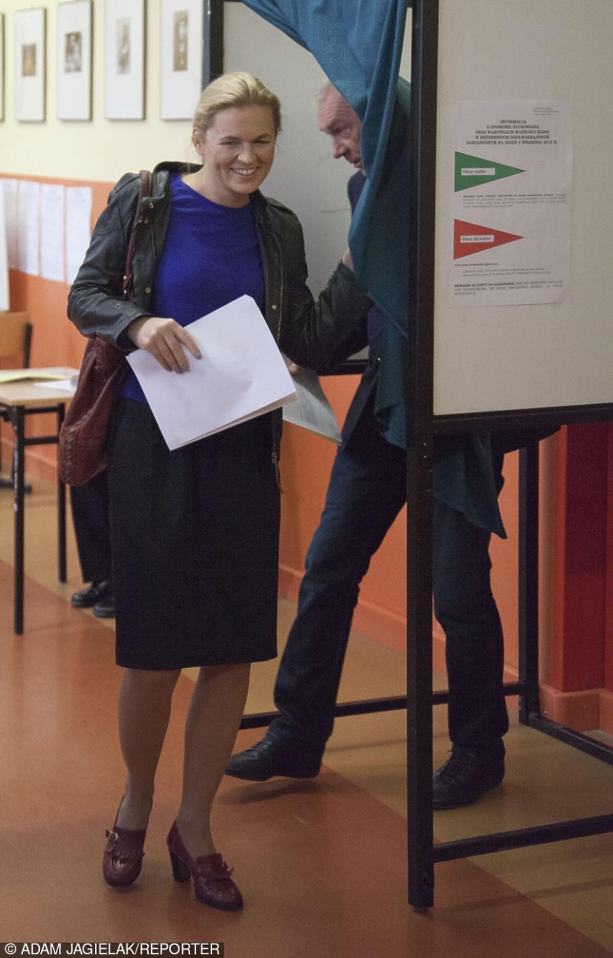 Barbara Nowacka w kobaltowej bluzce i skórzanej kurtce trzyma kartę do głosowania w wyborach parlamentarnych 2015