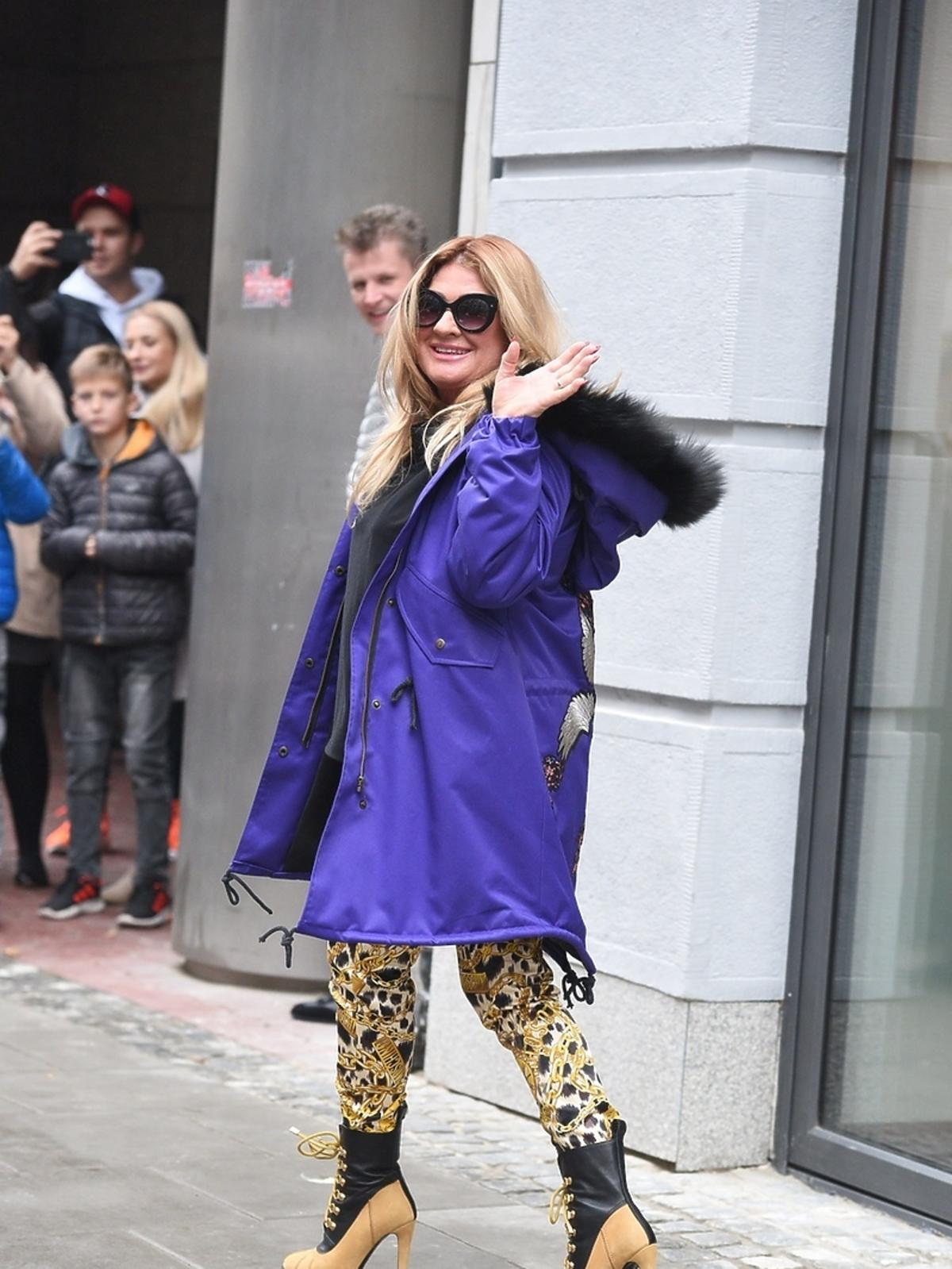 Beata Kozidrak w fioletowej kurtce i wzorzystych spodniach