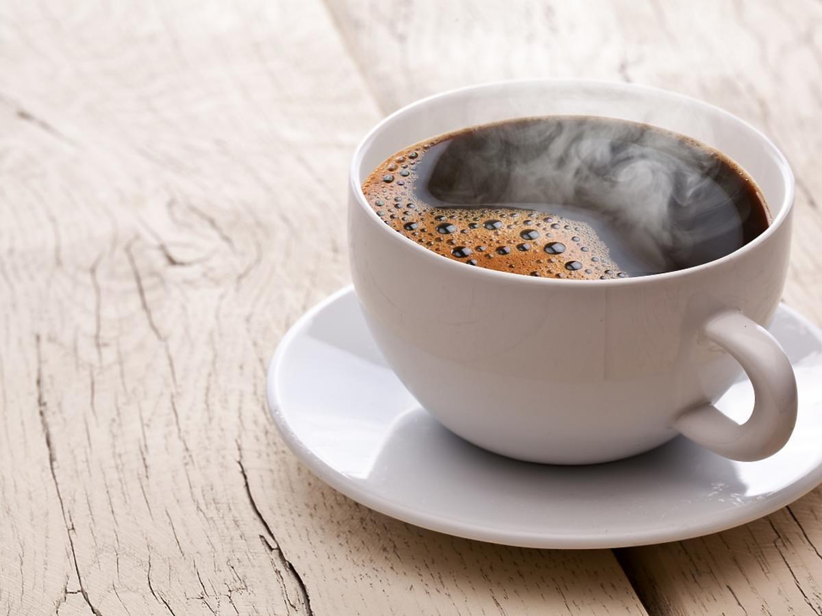 biała filiżanka z czarną kawą