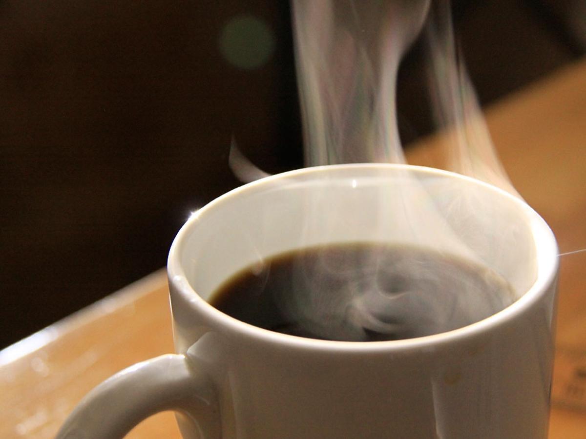 biały kubek z gorącą kawą