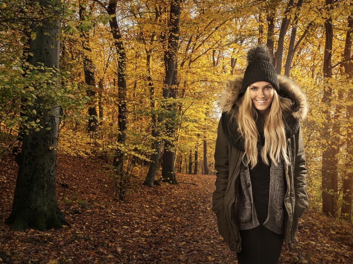 Blondynka w kurtce parce z kapturem na tle jesieni