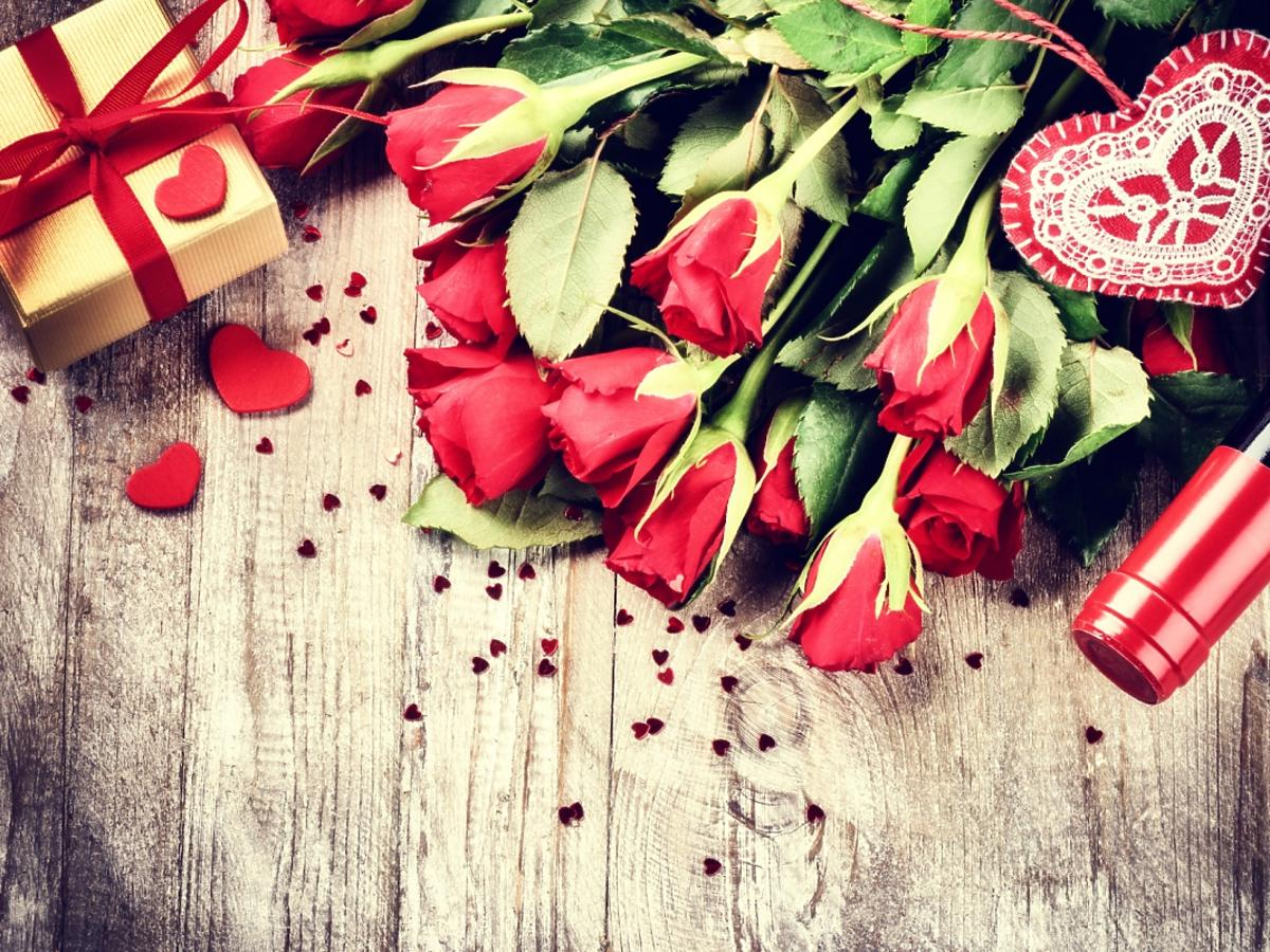 bukiet czerwonych róż i butelka wina
