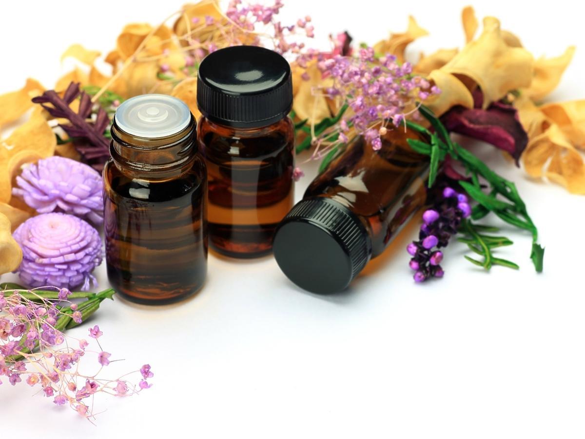 buteleczki z olejkiem na tle kwiatów