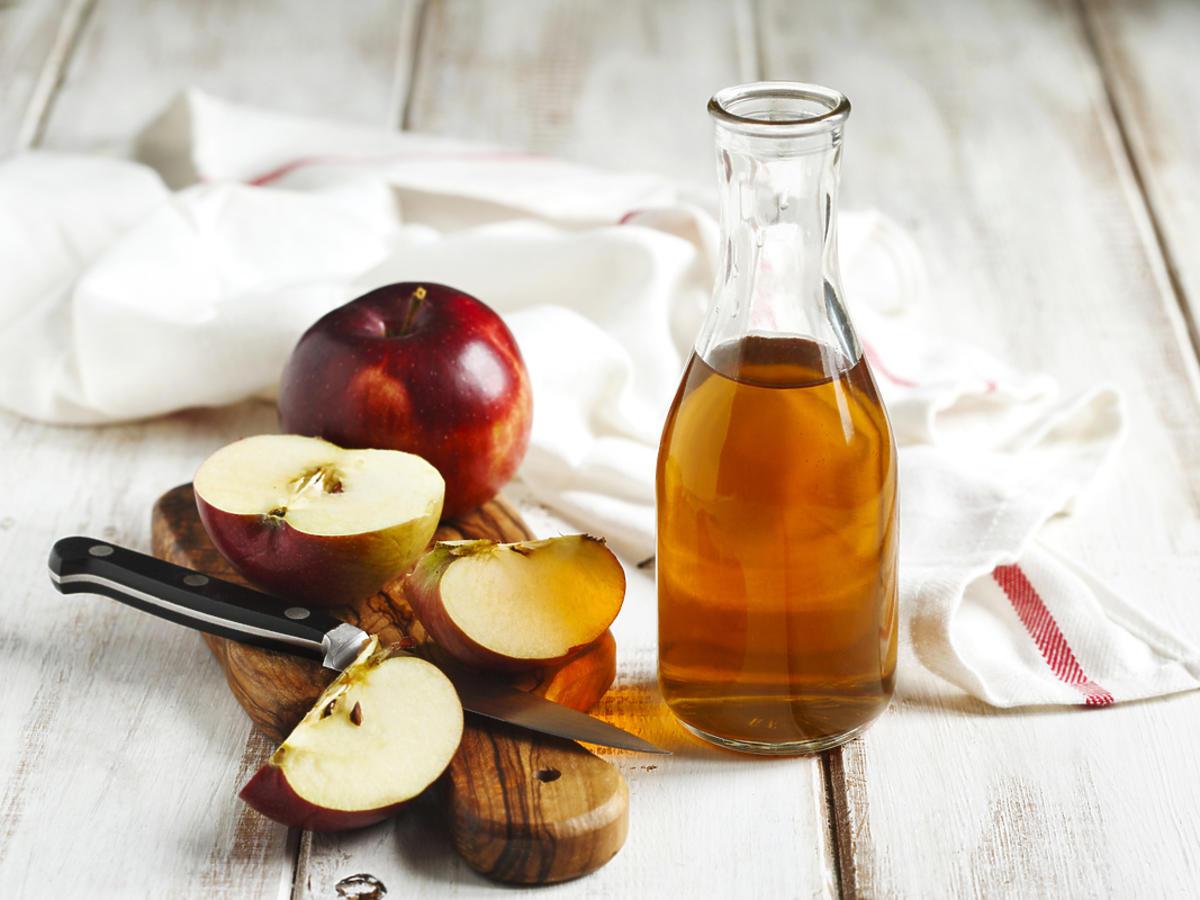 butelka z octem jabłkowym i jabłka