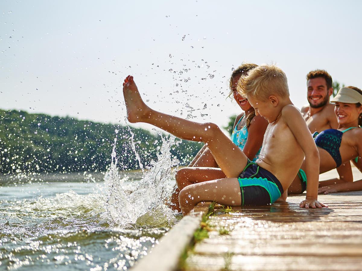 Cała rodzina spędza czas nad jeziorem.
