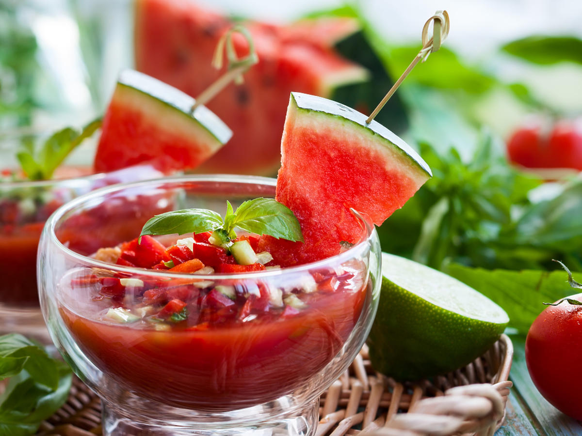 chłodnik z pomidorów w przezroczystej misce, ozdobiony kawałkami arbuza