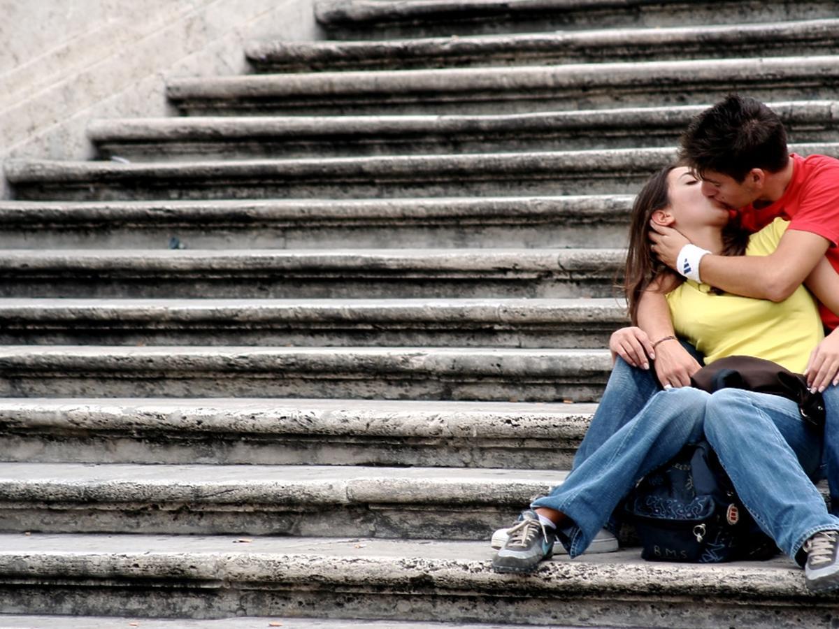 chłopak całuje dziewczynę na schodach