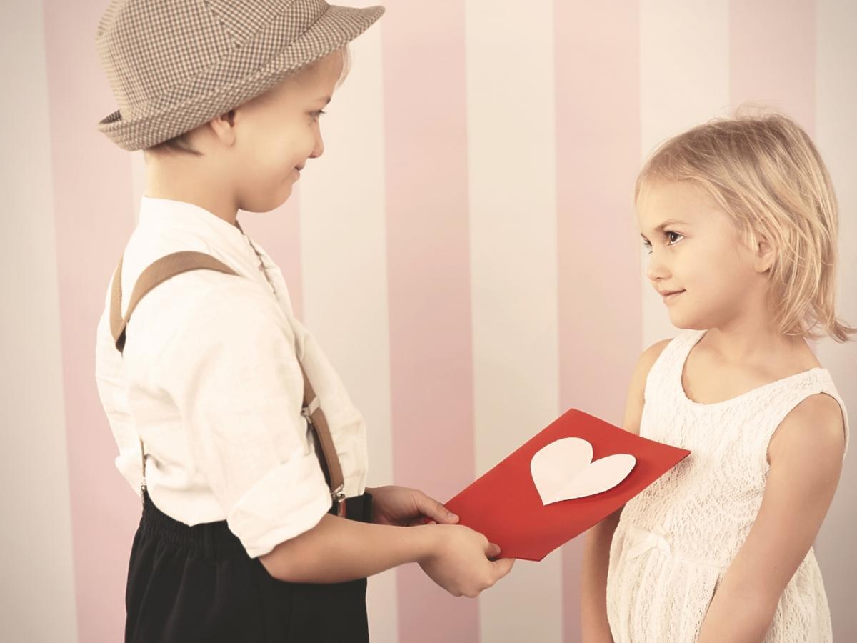 Chłopiec daje dziewczynce walentynkową kartkę
