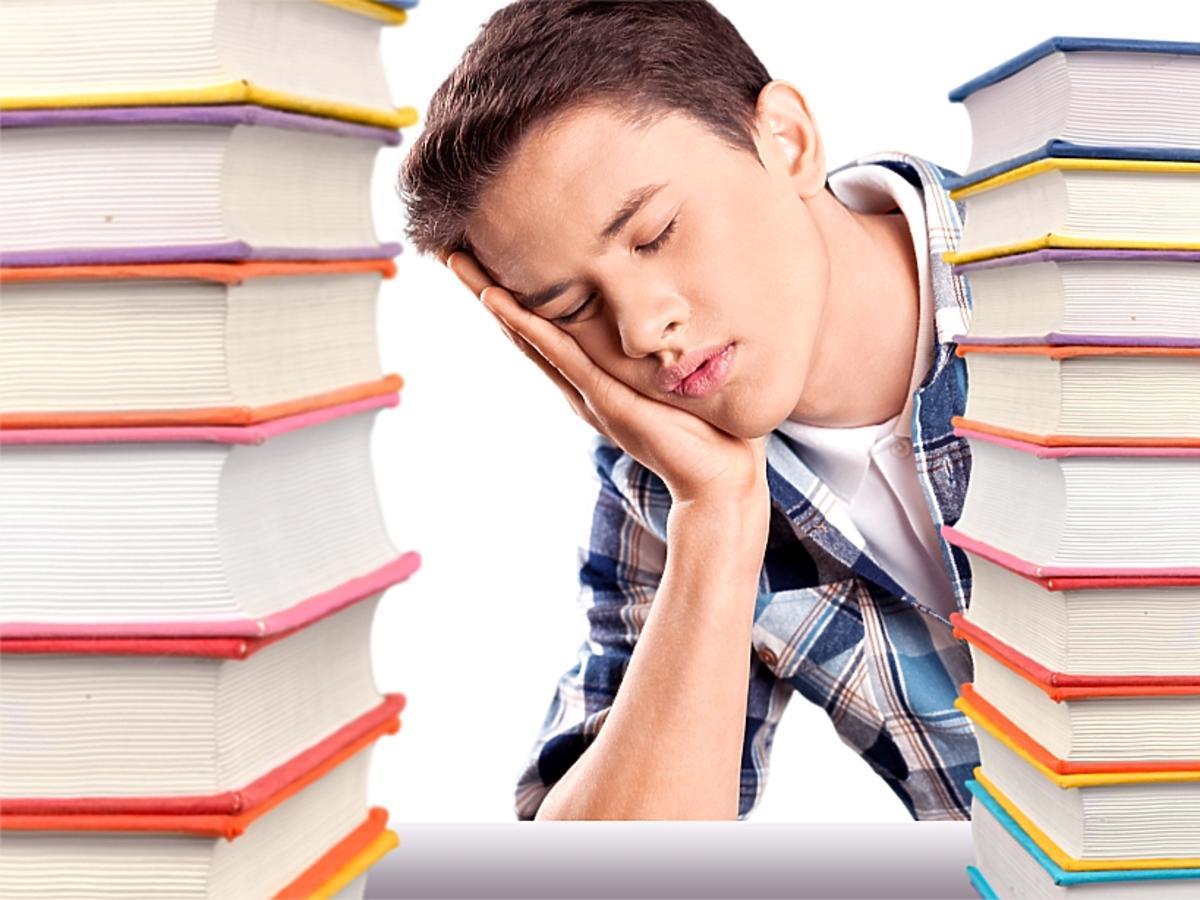 Chłopiec przysypia przy książkach