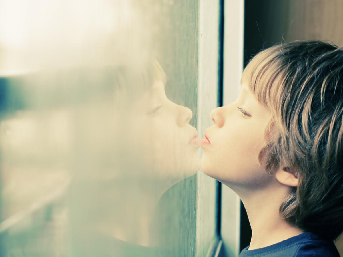 Chłopiec stoi przy oknie