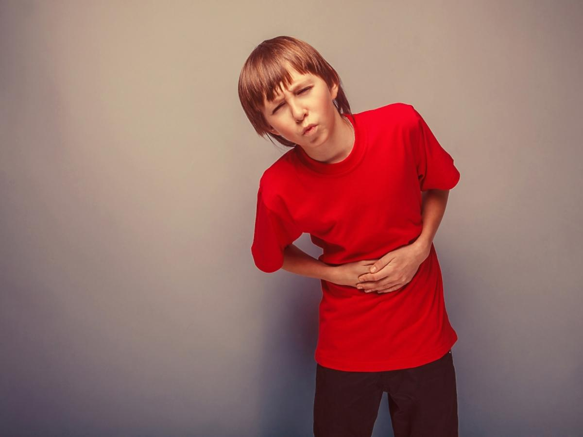 chłopiec trzymający się za brzuch