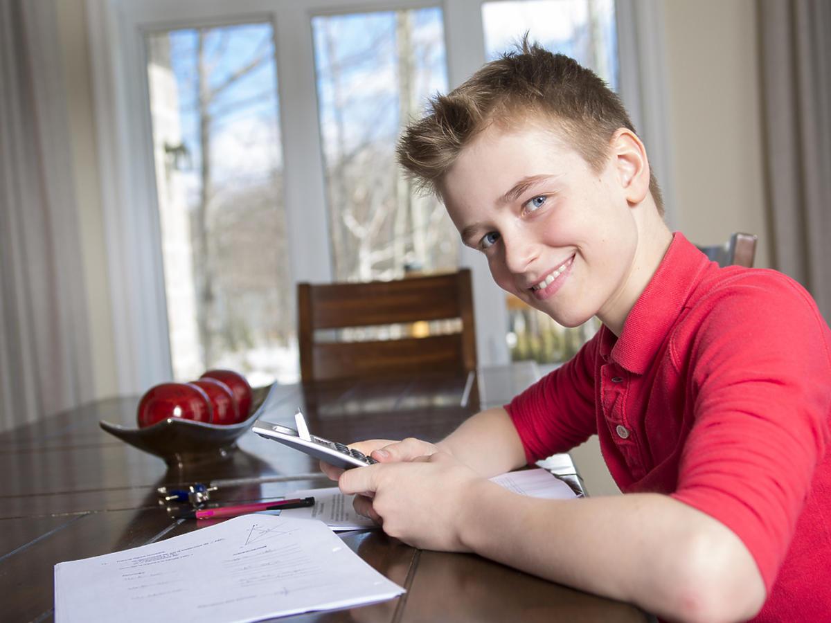 Chłopiec w okresie dojrzewania siedzi przy biurku