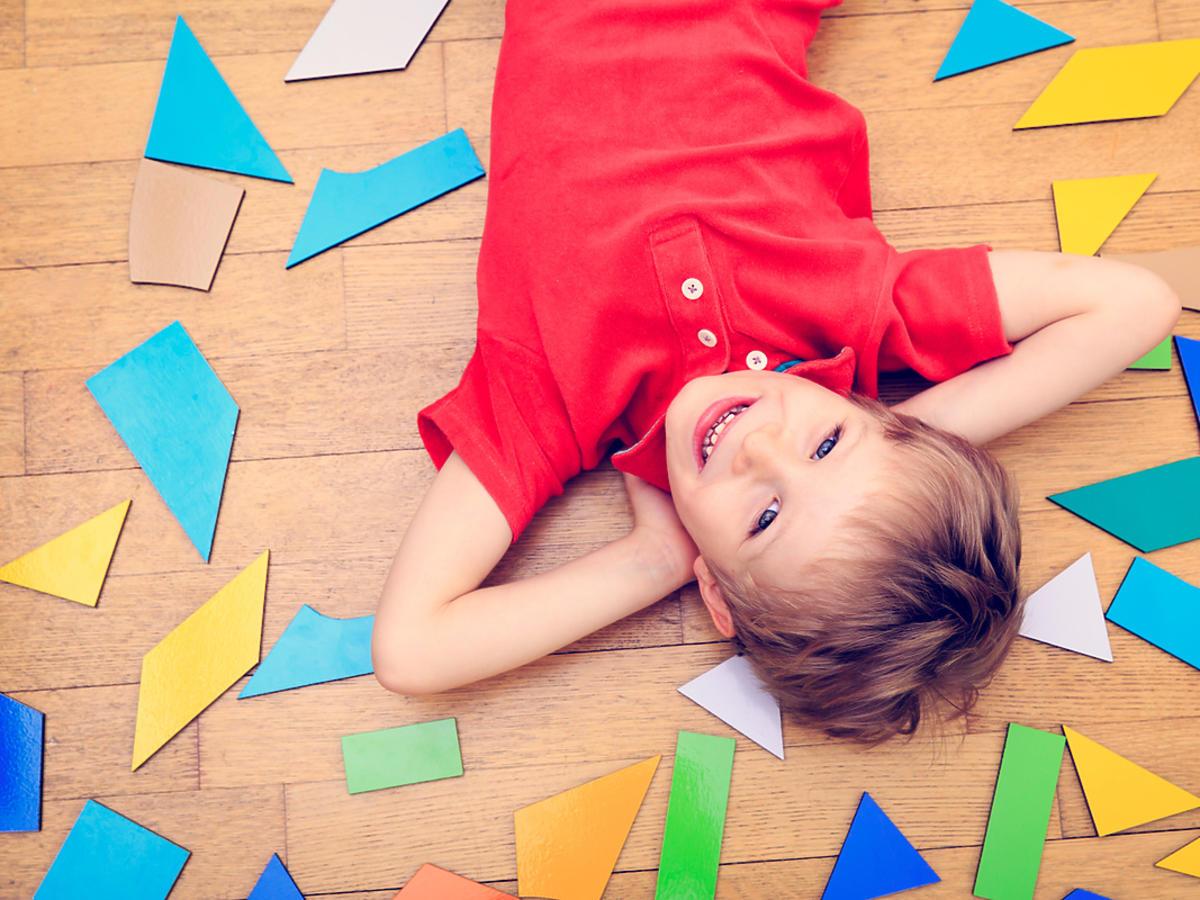 Chłopiec w wieku przedszkolnym odpoczywa na dywanie.