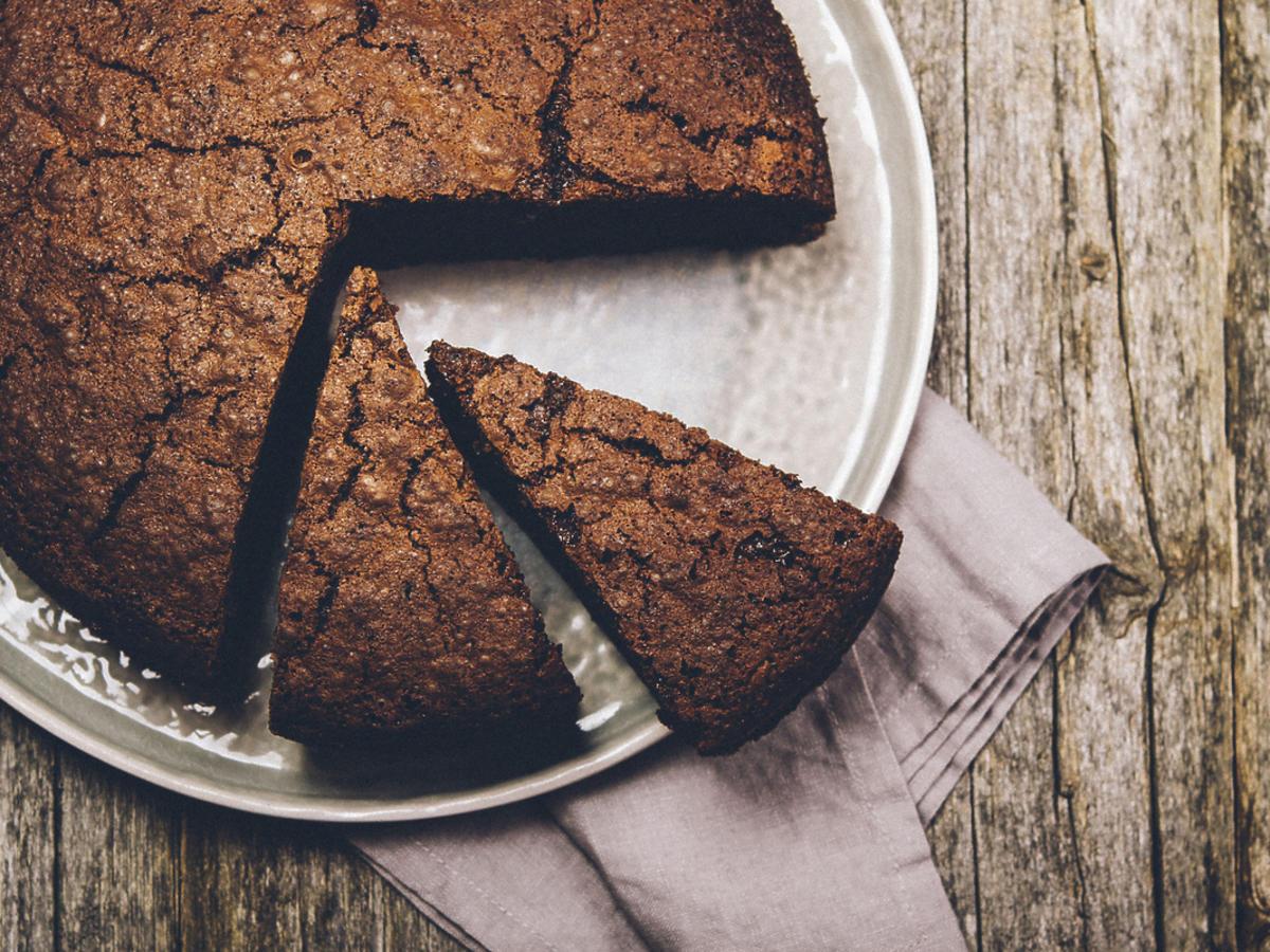 Ciasto czekoladowe z ukrojonym jednym kawałkiem.