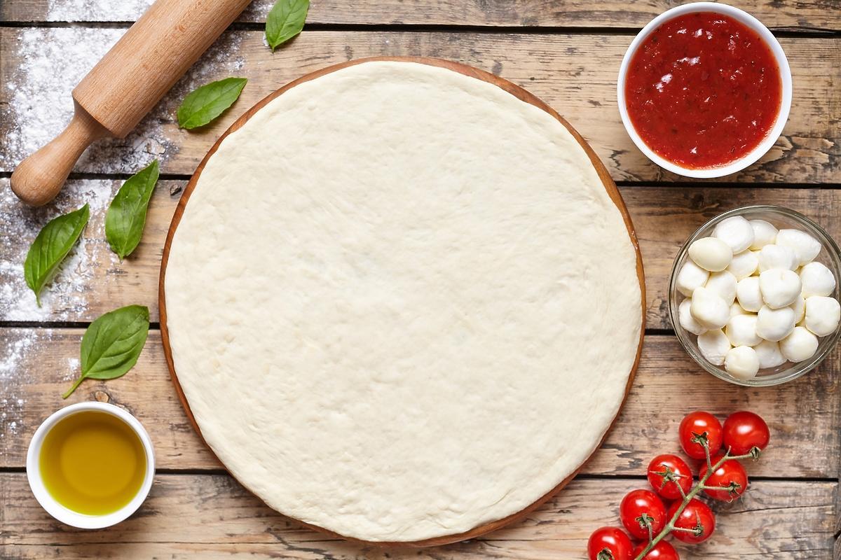 ciasto do pizzy na stole w otoczeniu wałka, miseczki z oliwą, bazylii i pomidorów