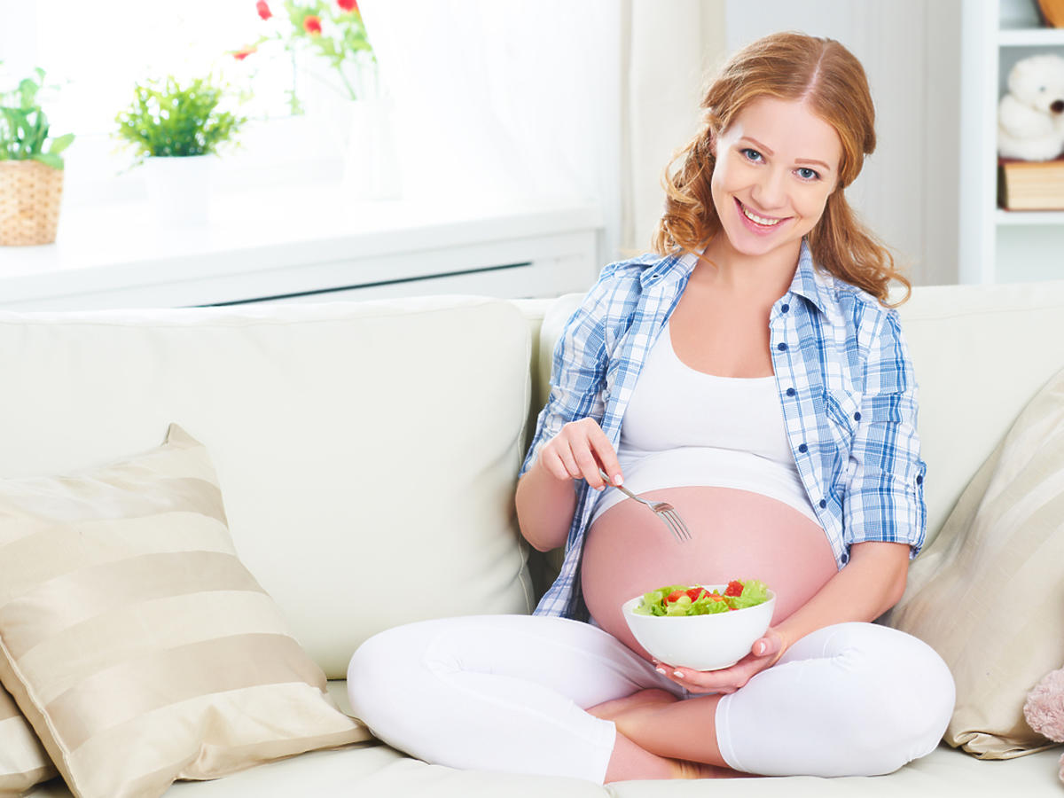 Ciężarna kobieta siedzi na kanapie, je sałatkę
