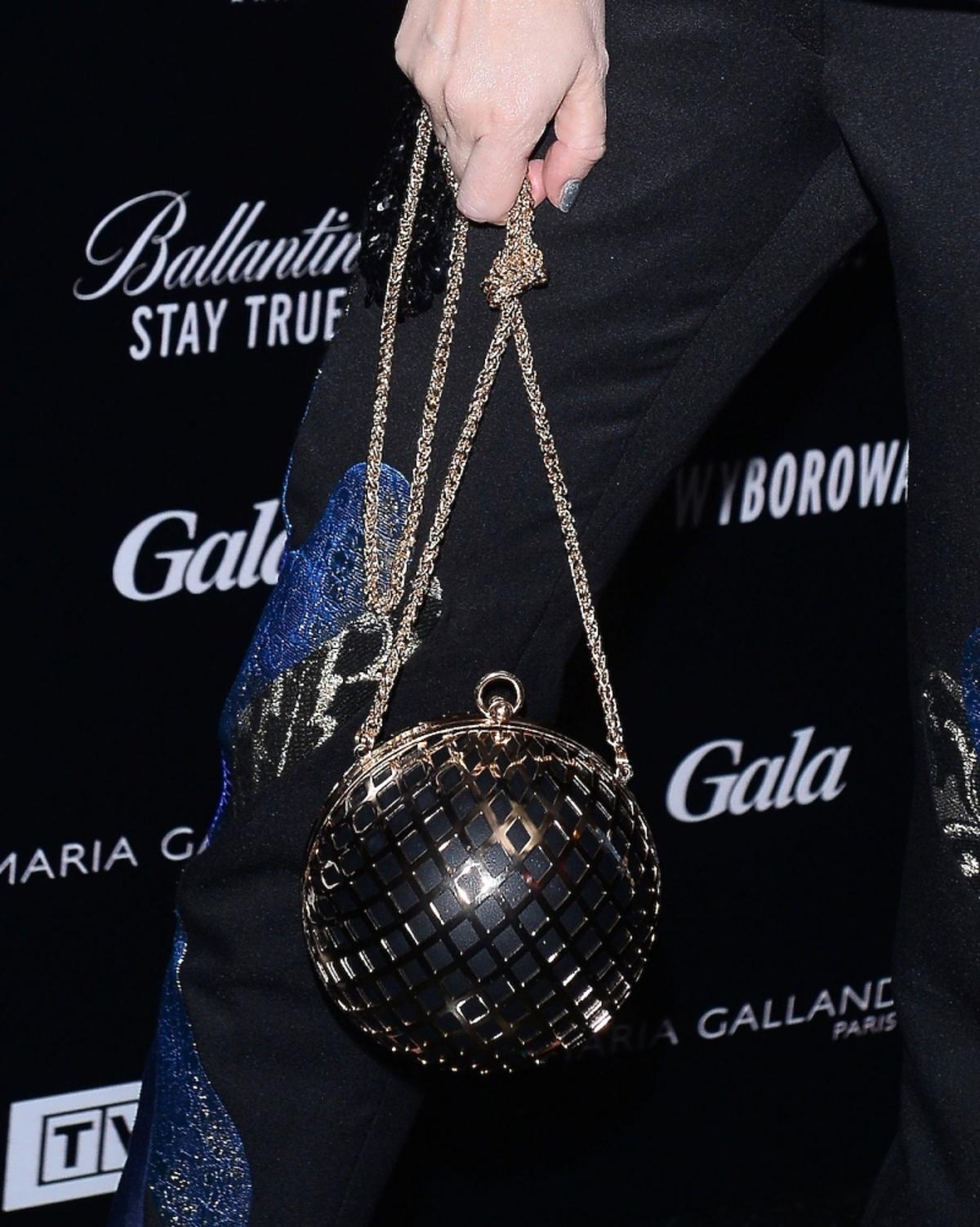 Czarna torebka w kształcie kuli na złotym łańcuszku