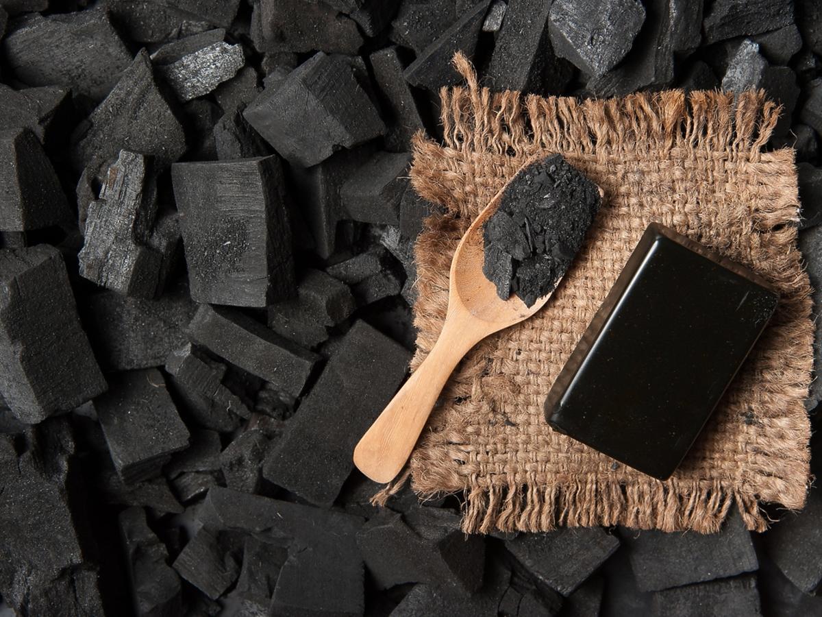 Czarne mydło leżące na kawałkach węgla drzewnego.