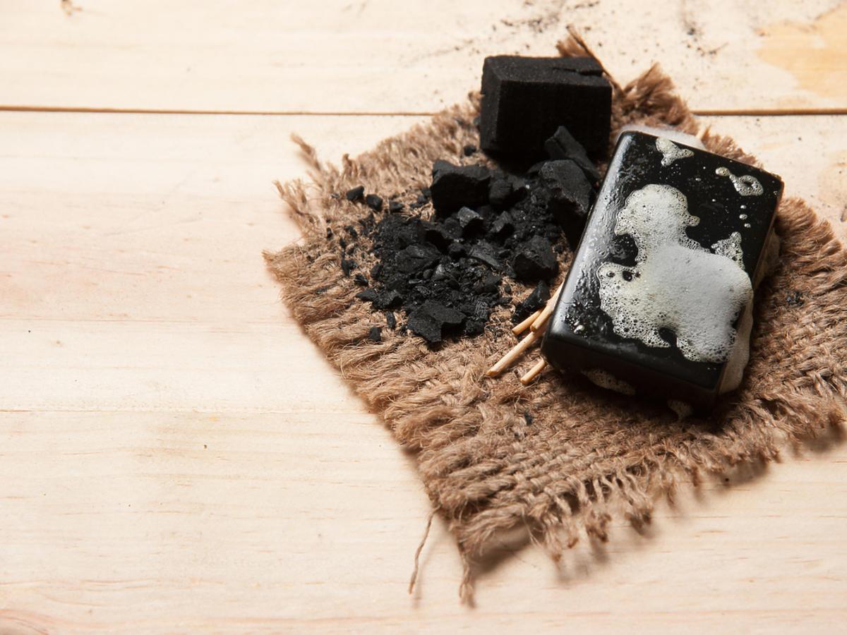 Czarne mydło położone na drewnianej tacy.