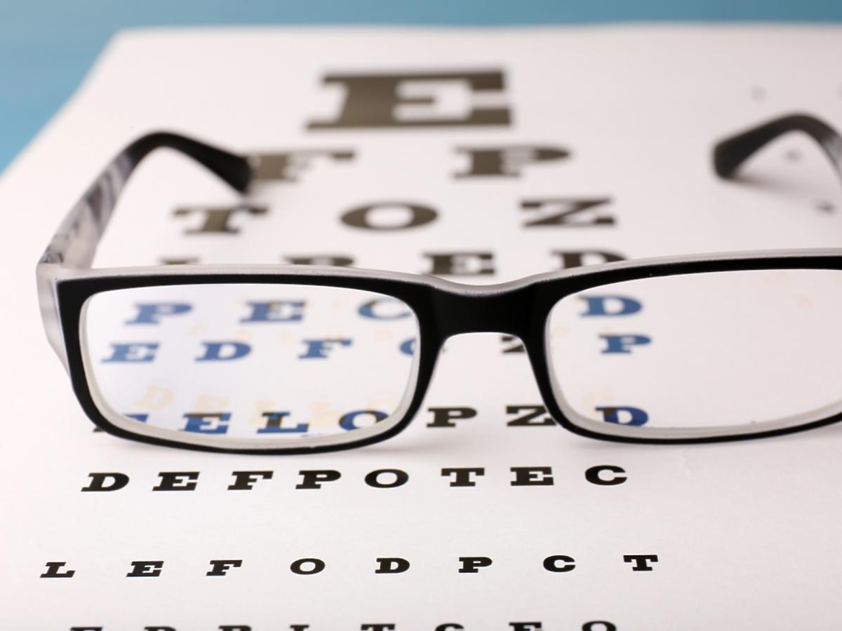 Czarne okulary leżą na alfabecie.