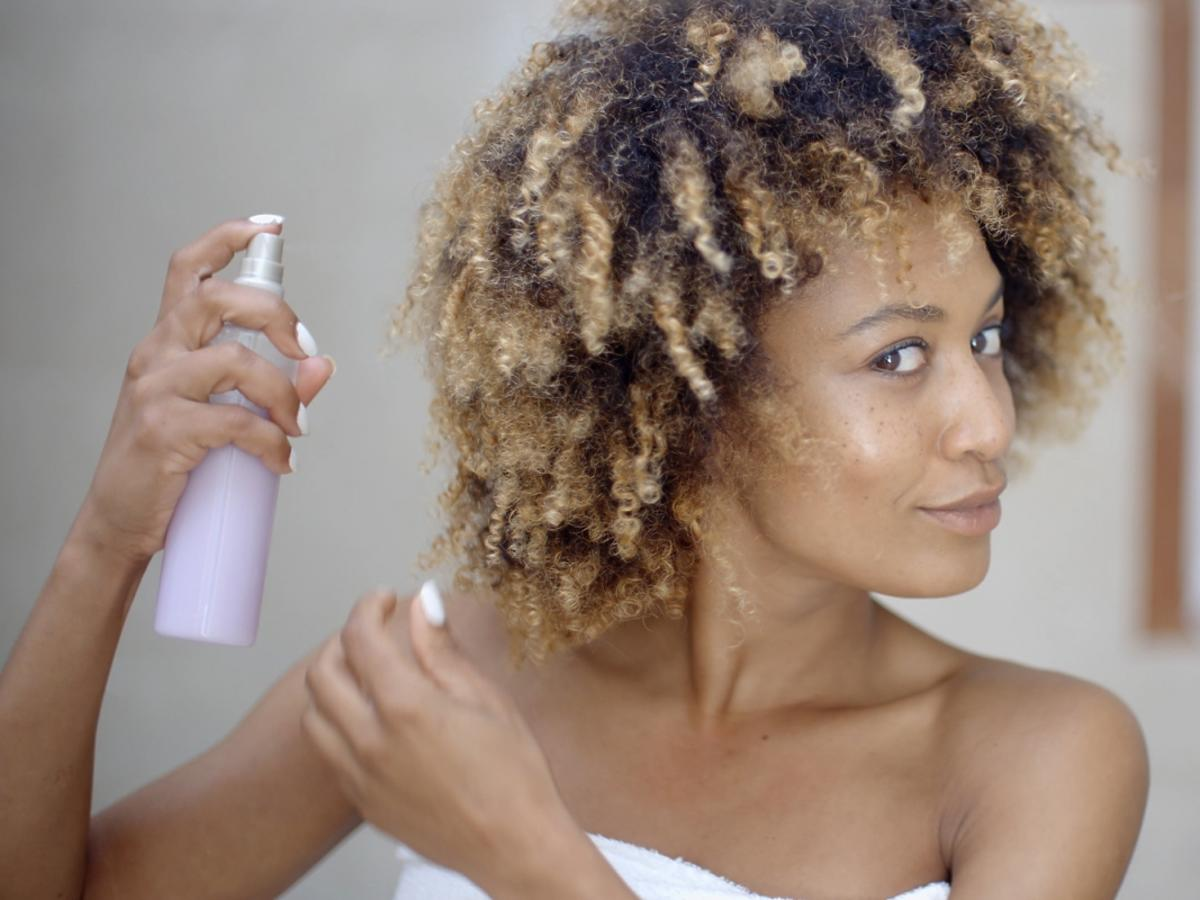 czarnoskóra kobieta spryskuje włosy