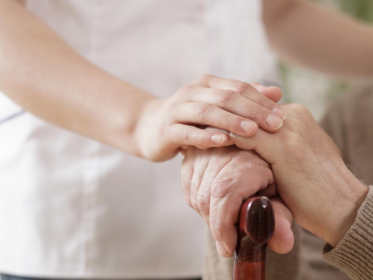 Człowiek kładzie dłoń na dłoni innego człowieka
