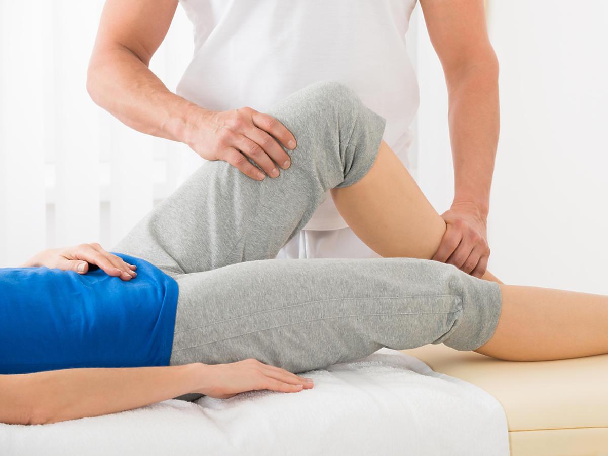 człowiek leżący na łóżku w trakcie masażu nóg