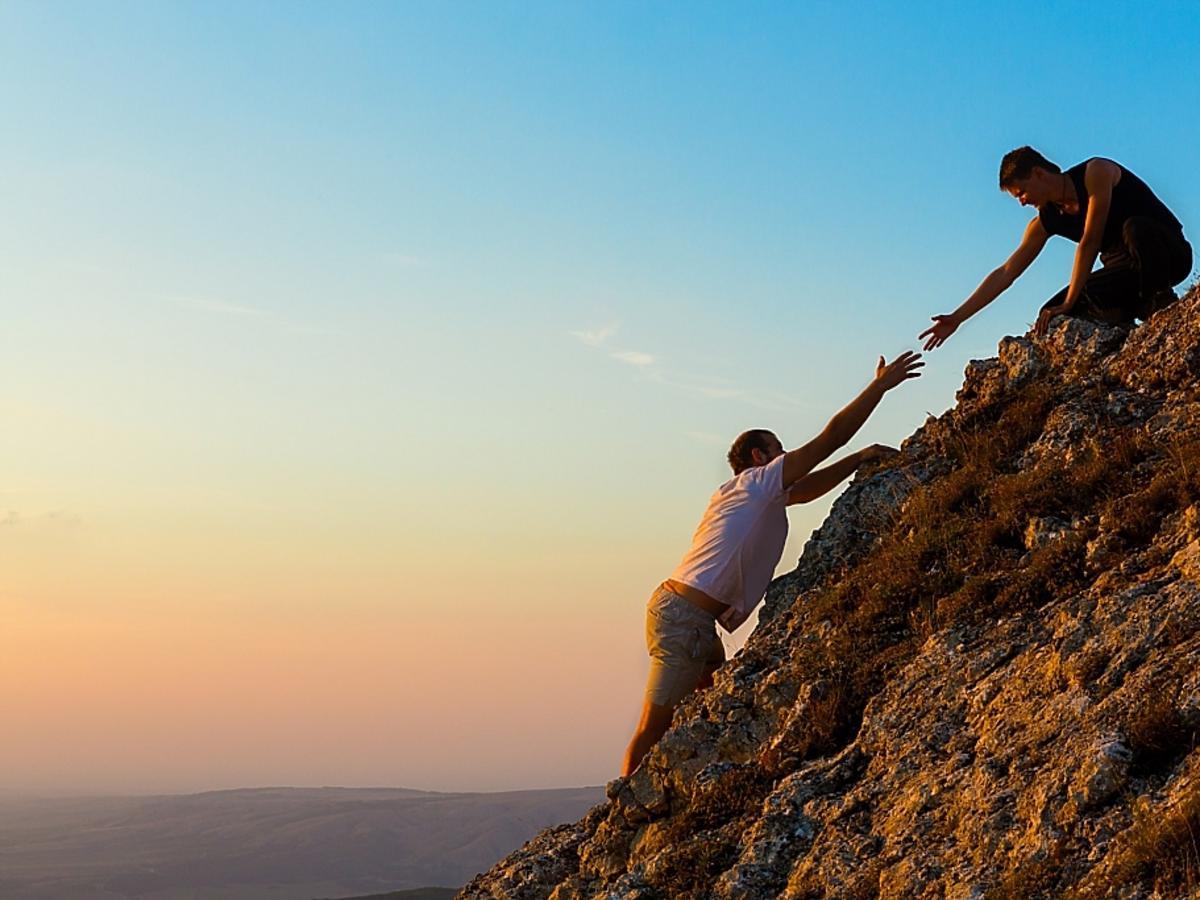 Człowiek podaje drugiemu człowiekowi pomocną dłoń.