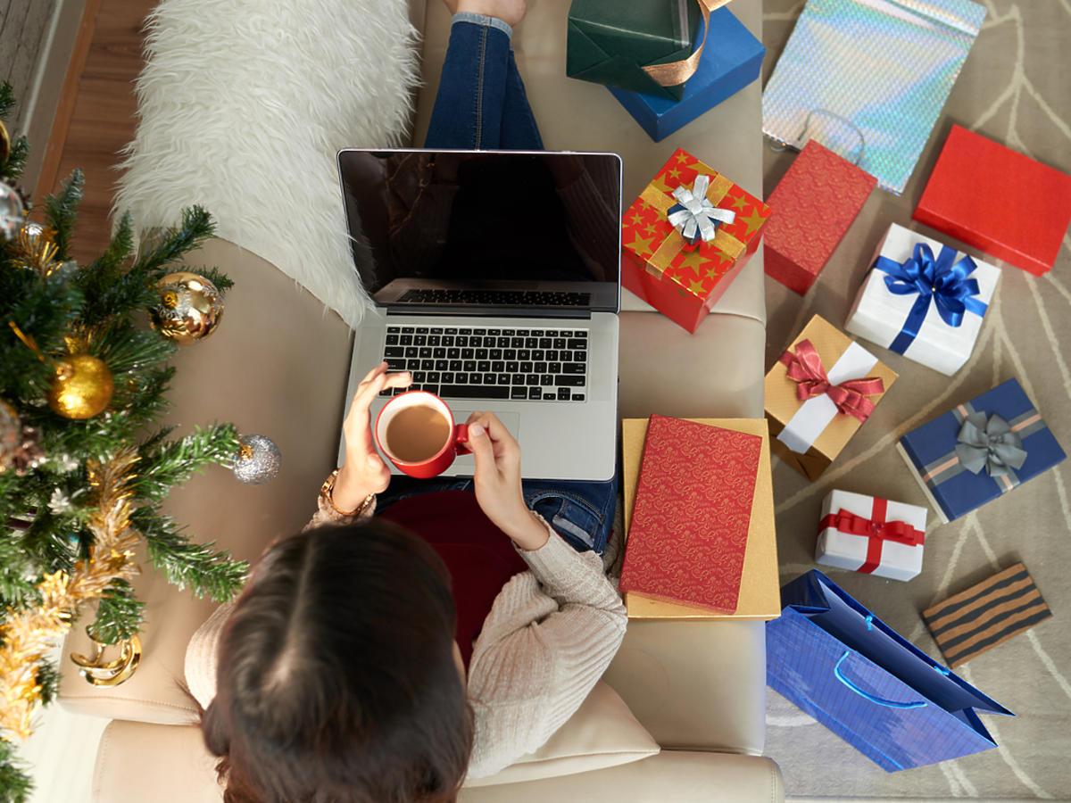 człowiek siedzący na kanapie w otoczeniu zapakowanych prezentów