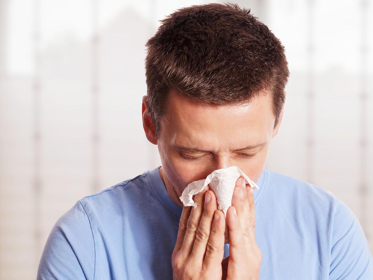 człowiek wycierający nos chusteczką