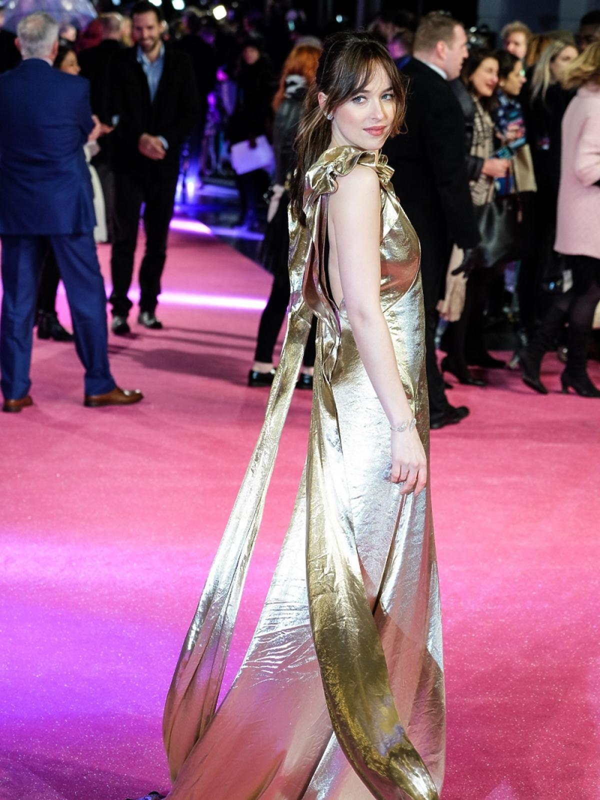 Dakota Johnson stoi bokiem w długiej złotej sukni na różowym dywanie