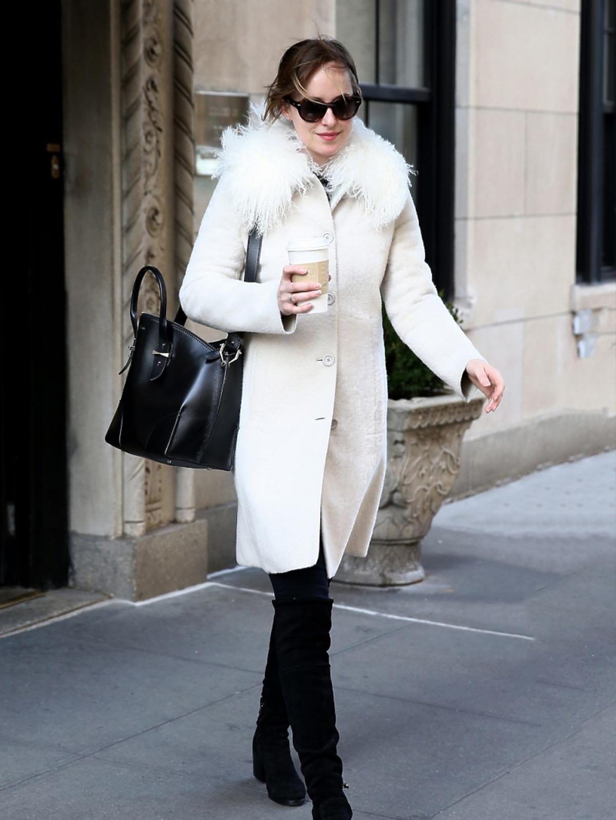Dakota Johnson w białym płaszczu i czarnych spodniach z kubkiem