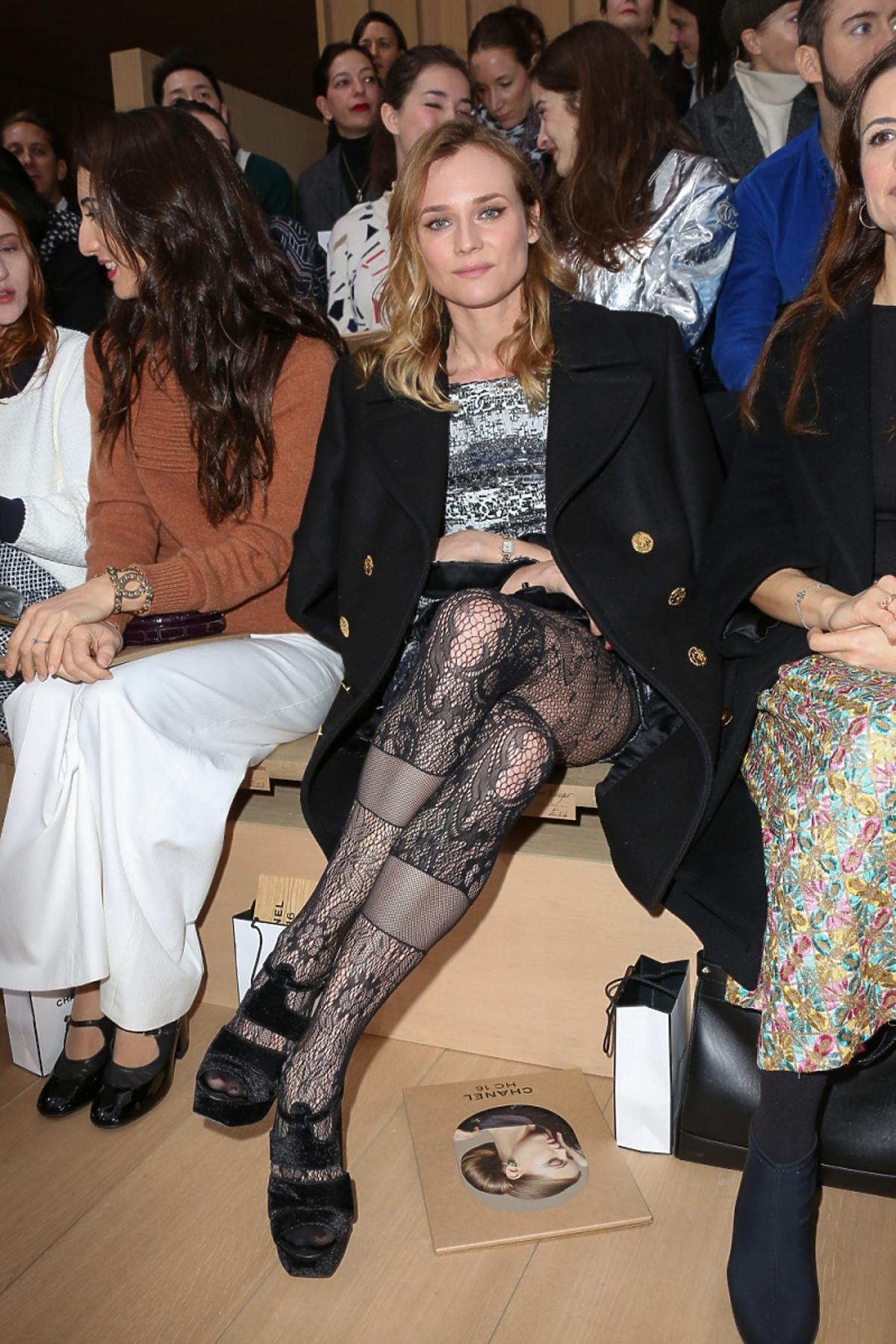 Diane Kruger siedzi na widowni ze skrzyżowanymi nogami w koronkowych rajstopach