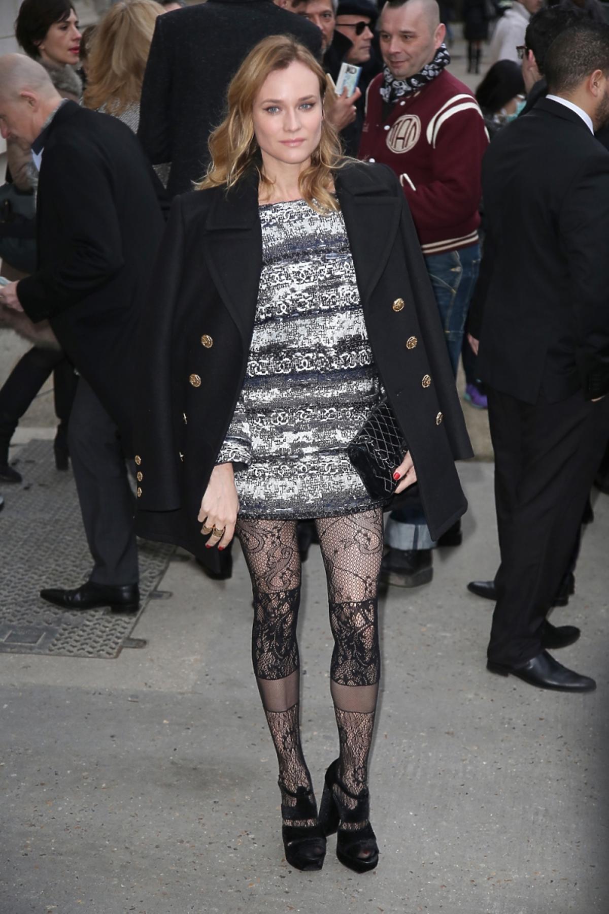 Diane Kruger w czarnym płaszczu, szarej sukience i koronkowych rajstopach