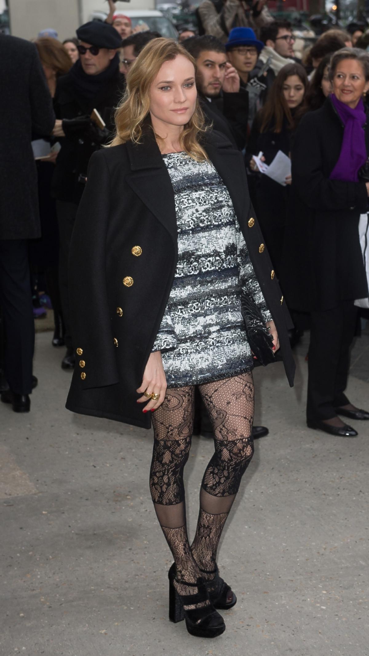 Diane Kruger w koronkowych rajstopach, sandałach, sukience w paski i czarnym plaszczu