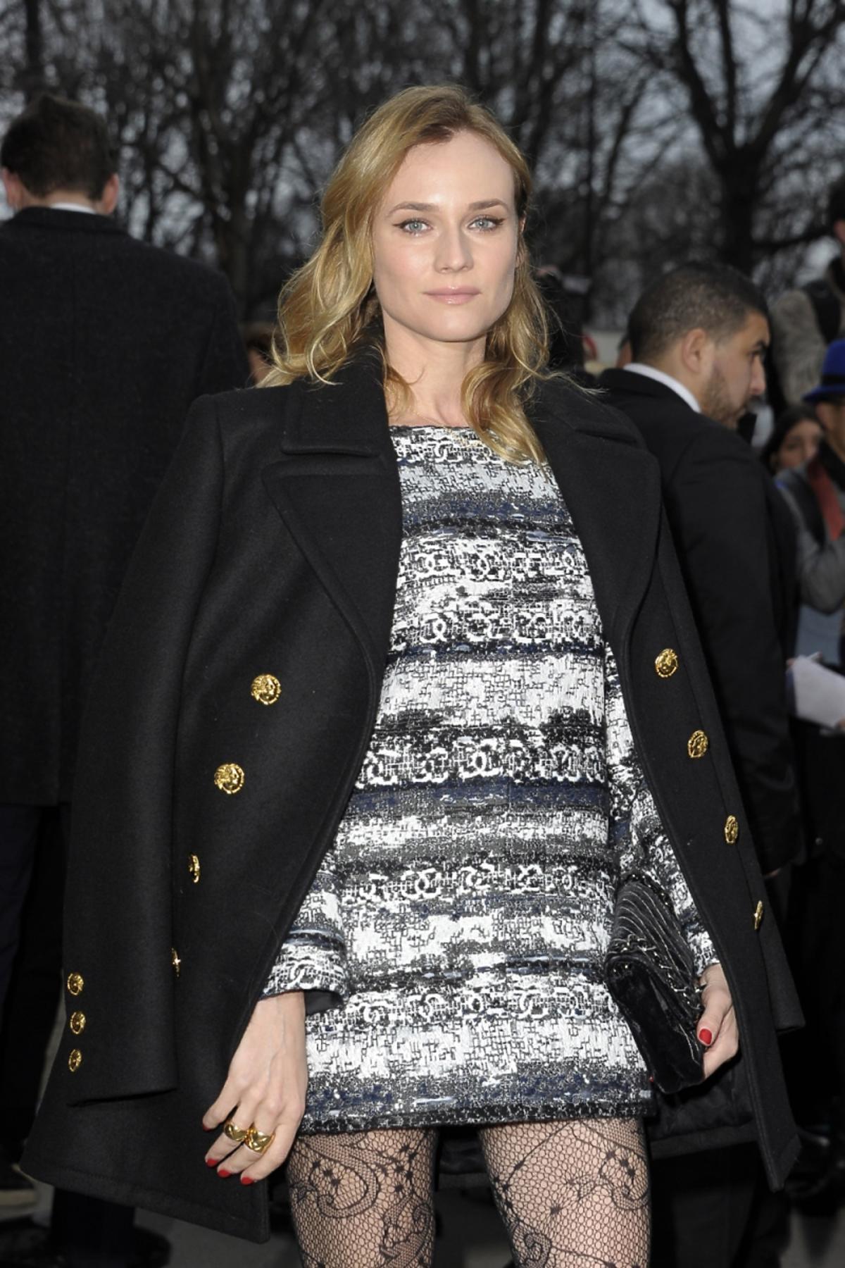Diane Kruger w koronkowych rajstopach, sukience w paski i czarnym plaszczu militarnym