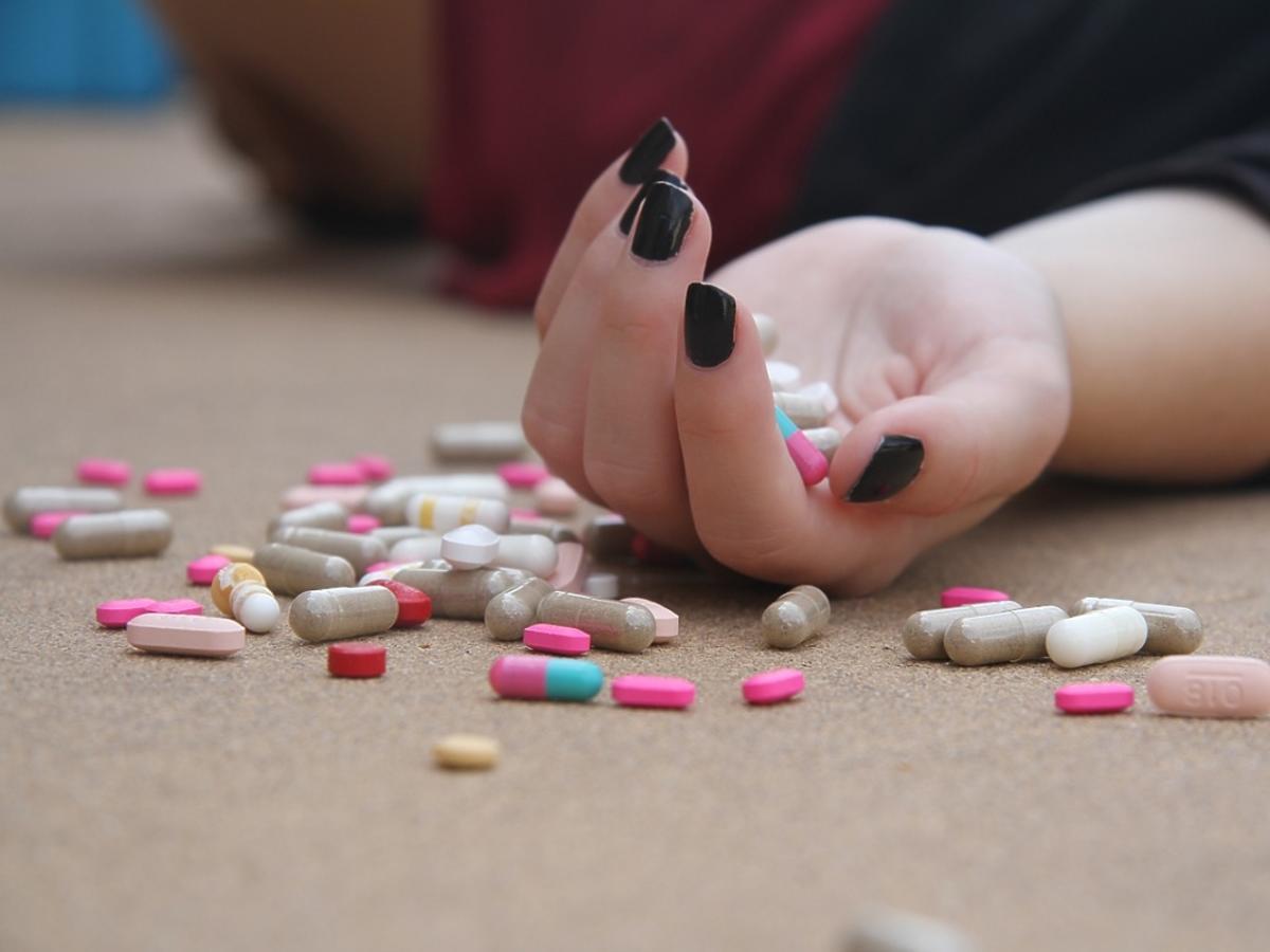 Dłoń i rozsypane tabletki